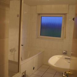 Ein altes Bad mit Wanne und Dusche